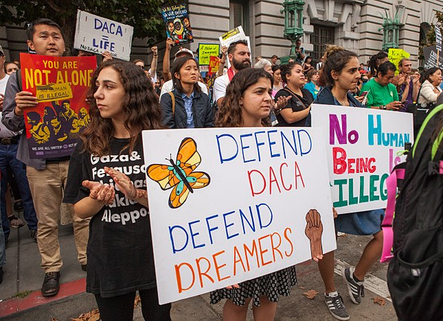 """Picture of protesters holding sign that reads """"Defend DACA, Defend Dreamers"""""""